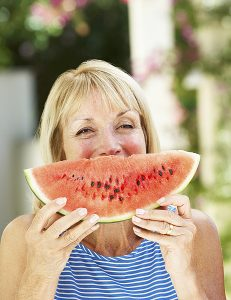 Mother And Adult Daughter Enjoying Slices Of Water Melon