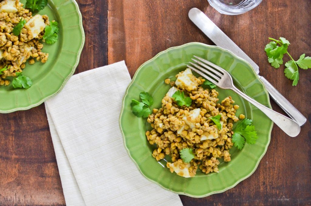 """""""green plate with lentils on a wooden table"""""""