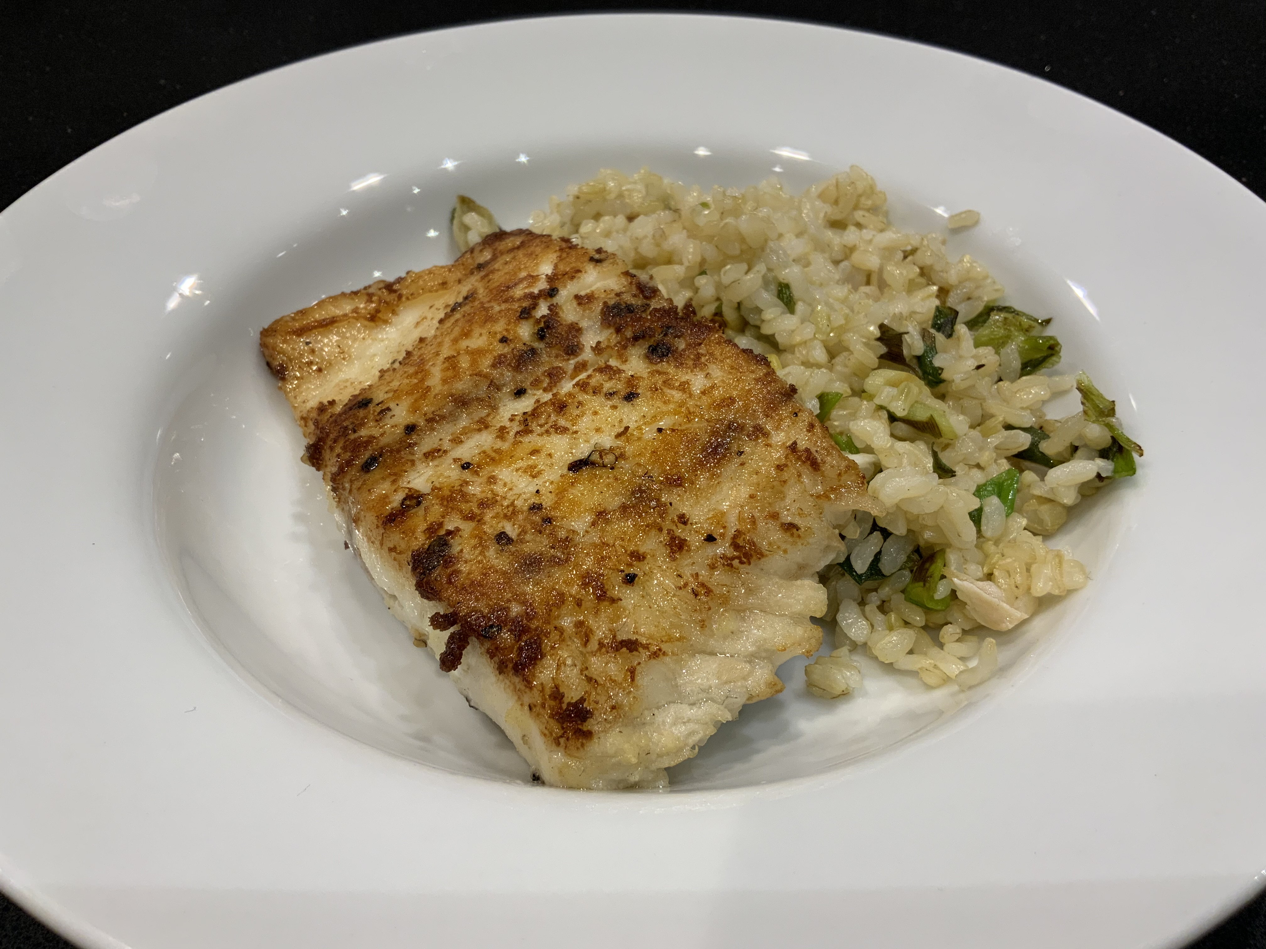 """White dinner plate with seared fish and rice"""