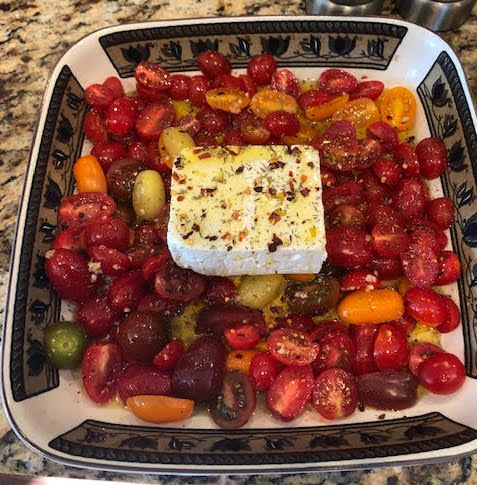 A decorated baking dish filled with cherry tomatoes and a block of feta cheese sitting on a countertop.