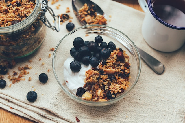 A bowl of yogurt and granola topped with blueberries and a cup of black coffee on a tablecloth.