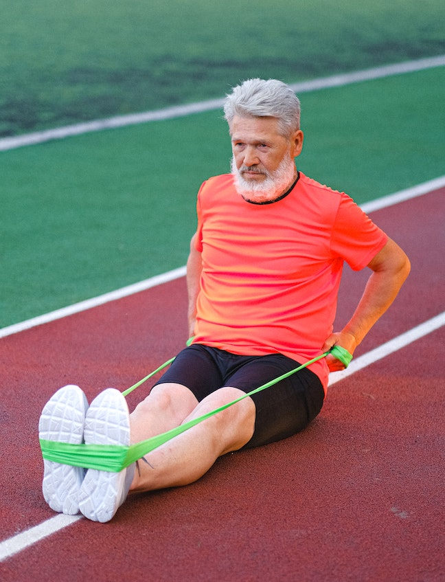 Caucasian older male sitting on a rubber track doing resistance band exercise.
