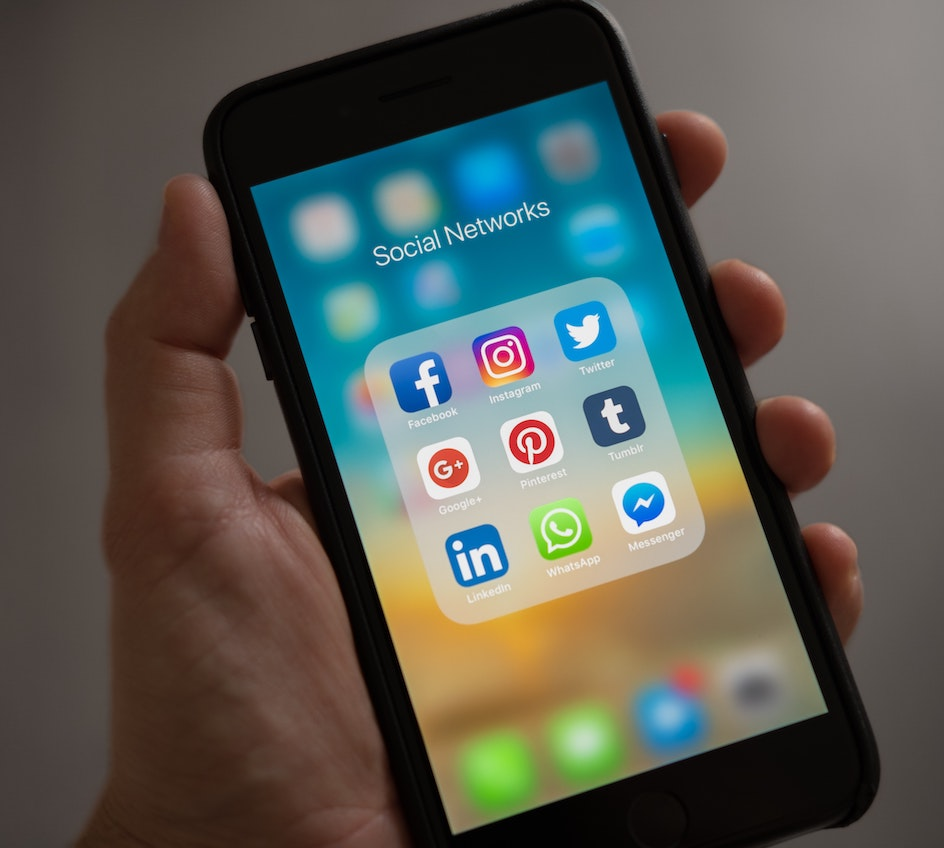 Caucasian hand holding an iphone showing a folder of Social Network apps.