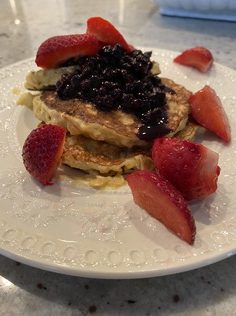 A white plate with a small stack of pancakes topped with fruit.