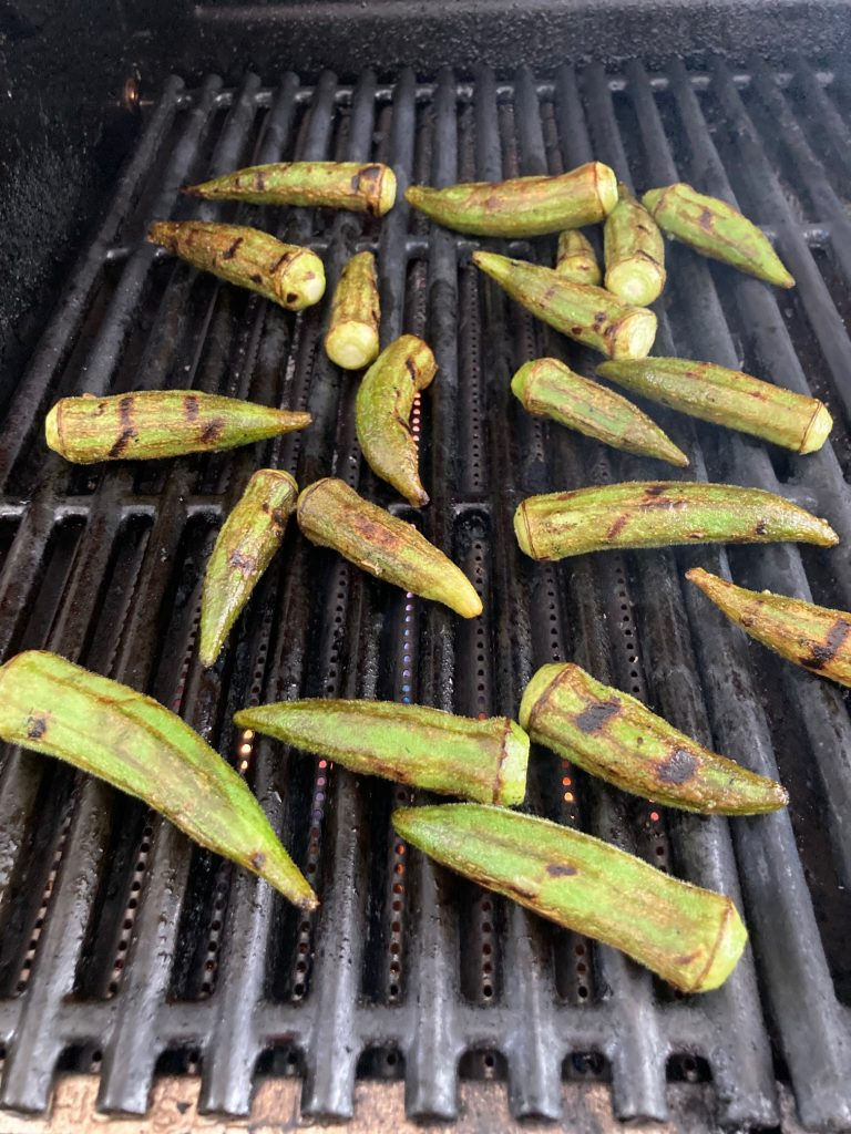 Whole okra on an outdoor grill grate