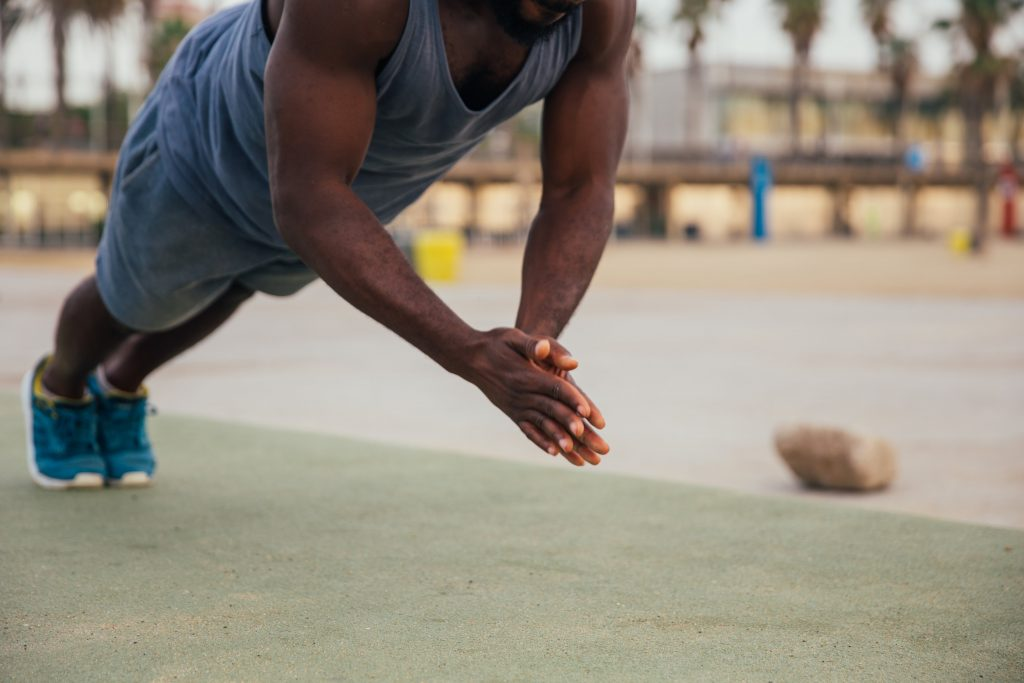athletic black male performing a clapping push up mid-air with hands together.